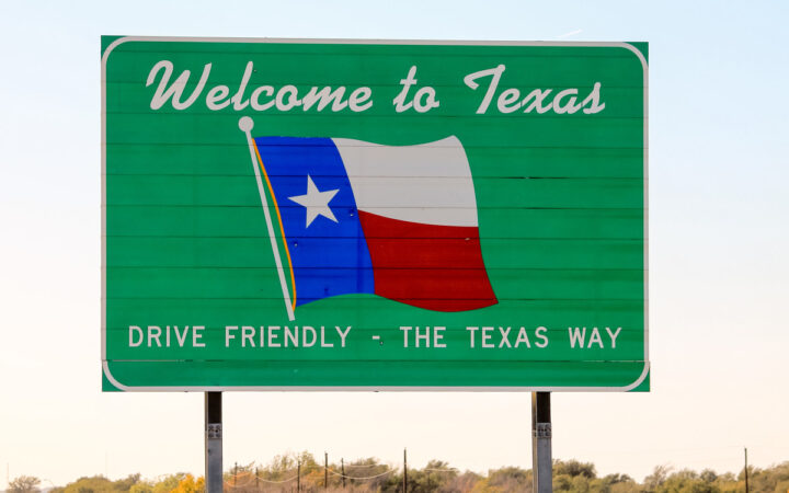 """Texas road sign upon entering the state that says """"Welcome to Texas"""" and """"Drive Friendly - The Texas Way"""""""