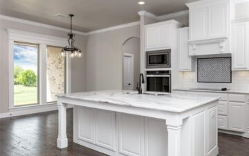 photo of a kitchen interior of a home for sale showing a counter top, oven, and open window with view of back yard