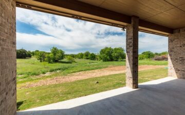 photo from the interior of a garage facing sprawling land surrounded by trees